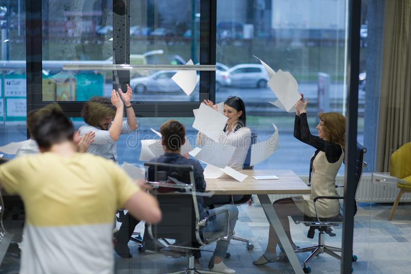 Startup group of young business people throwing documents royalty free stock images