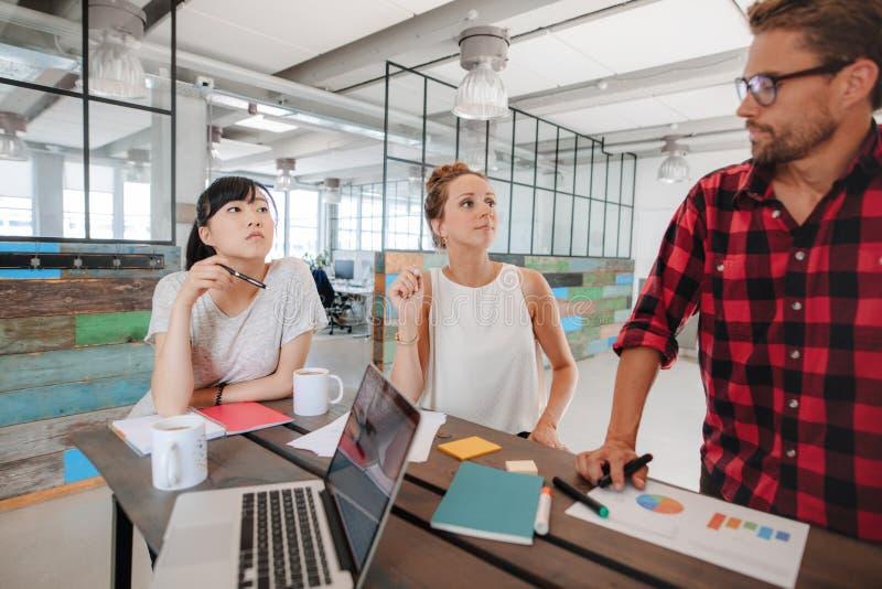 Startup möte runt om en tabell i modernt kontor royaltyfria foton