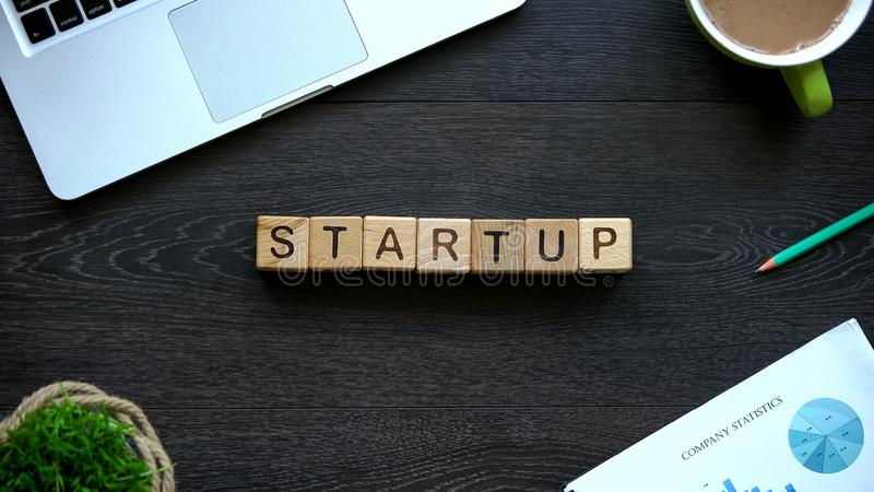 Startup word made of wooden cubes, new project and private company, business. Stock photo royalty free stock images