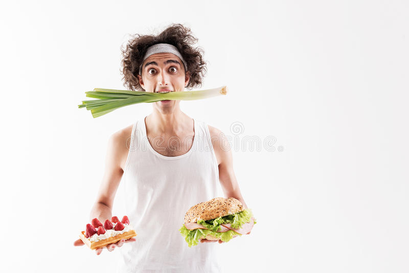 Starving thin guy choosing healthy eating stock photography