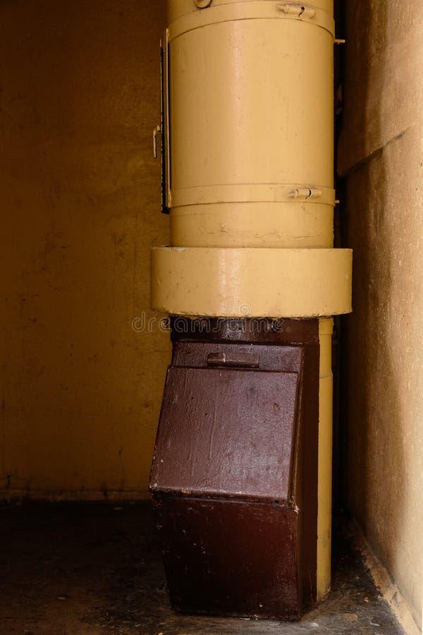 Stary śmieciarski korytko w budynku mieszkaniowym z tanimi mieszkaniami - banialuki korytko w Radzieckim bloku mieszkalnym obraz royalty free