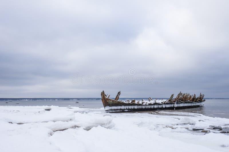 Stary łamający łódkowaty wrak i skalista plaża w wintertime Zamarznięty morze, evening lekką i lodowatą pogodę na brzeg lubi bajk obrazy stock