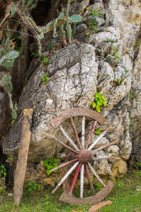 Stary łamający drewniany koło opiera up przeciw kamiennej ścianie furgon fotografia royalty free