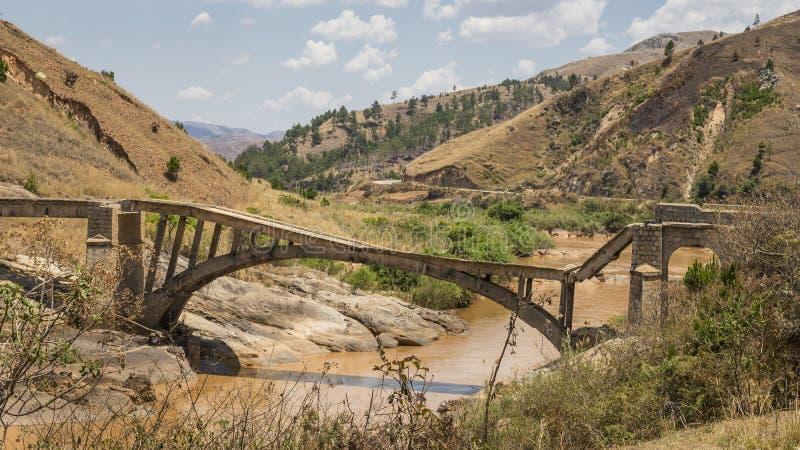 Stary łamający most na błotnistej rzece zdjęcie royalty free
