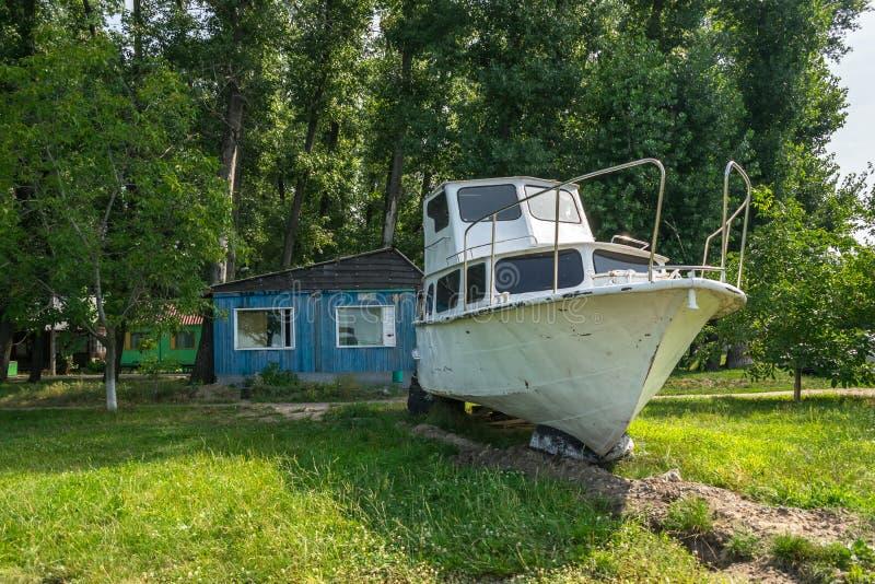 Stary żeglowanie jacht na ziemi Stary bielu silnika jacht wyrzucać na brzeg przy a zdjęcie royalty free
