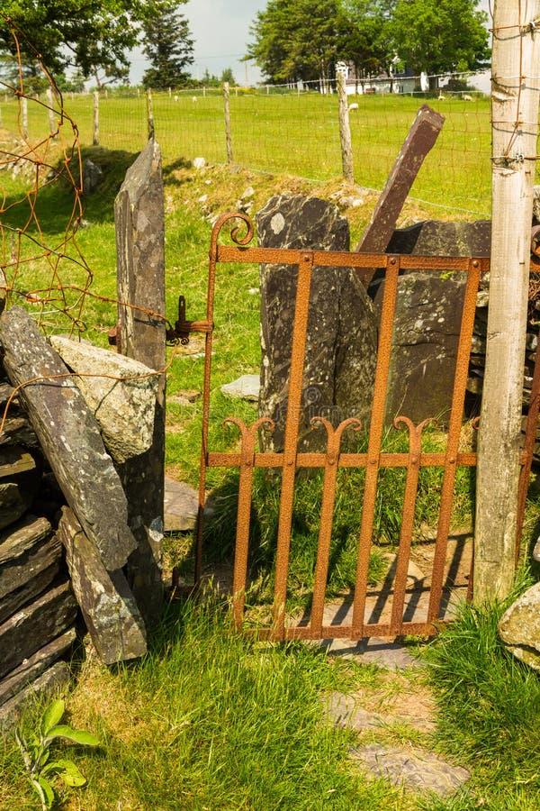 Stary żelazny brama przełaz w suchej kamiennej ścianie zdjęcia stock