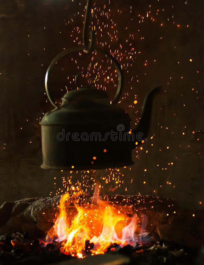 Stary żelazny czajnik na ogieniu fotografia stock