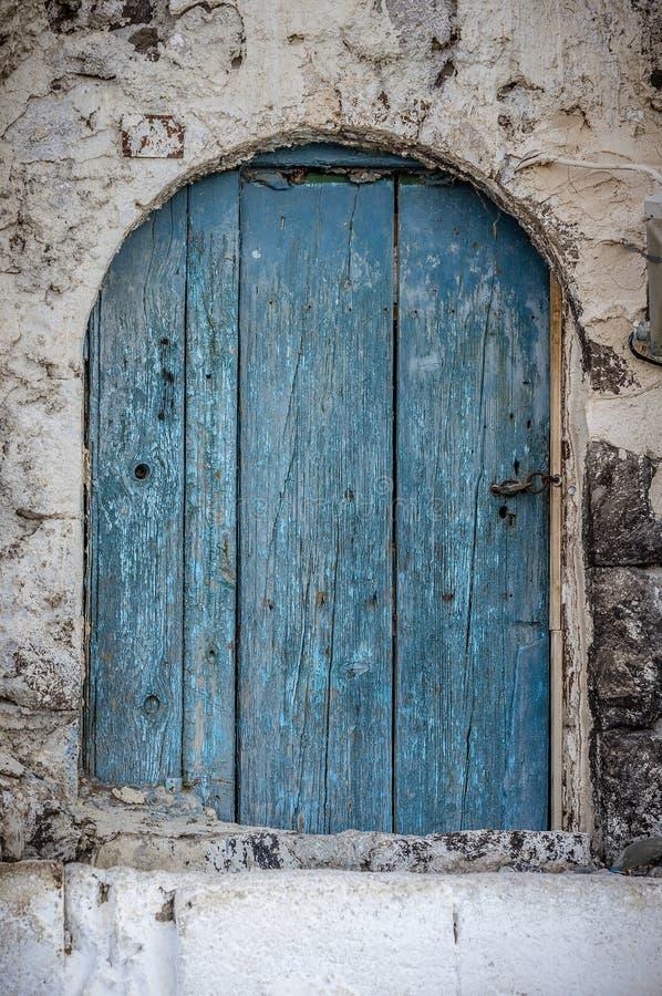Stary błękitny szalunku drzwi w scuffed ścianie fotografia stock