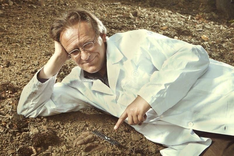 Stary badacz zakłada trylobit skamielinę na skalistej lokaci obraz stock