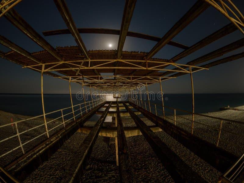 Stary betonowy molo na plaży przy nocą w blask księżyca fotografia stock