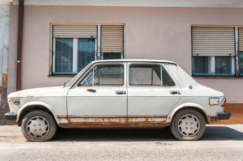 Stary biały ośniedziały Fiat Zastava 101 samochód robić w Kragujevac mieście, porzucającym na ulicie zdjęcia royalty free