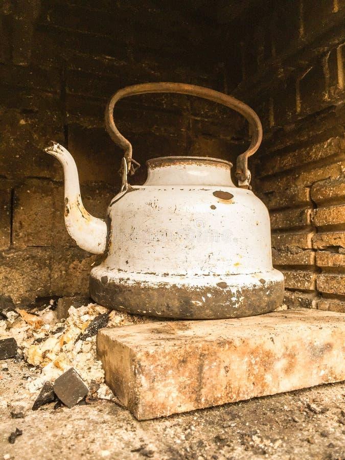 Stary biały powyginany czajnik w firebox fotografia stock
