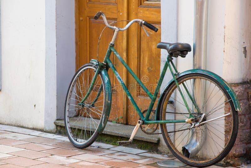 Stary bicykl przed domowym drzwi, tradycyjny tryb transport dla zdrowego życia zdjęcia stock