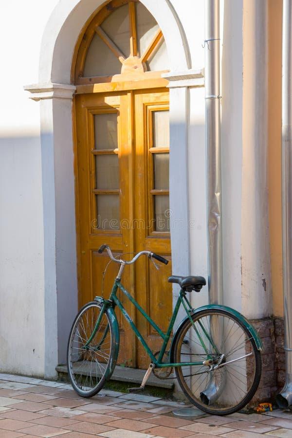 Stary bicykl przed domowym drzwi, tradycyjny tryb transport dla zdrowego życia obraz stock