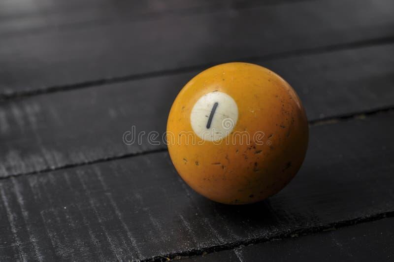 Stary 1 bilardowej pi?ki liczby pomara?czowy kolor na czarnym drewnianym sto?owym tle, kopii przestrze? obrazy royalty free