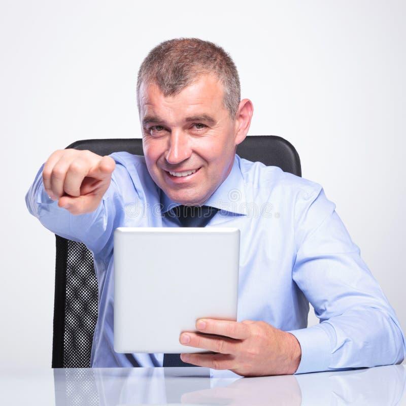Stary biznesowy mężczyzna przy biurkiem z ochraniacza wskazywać obraz royalty free