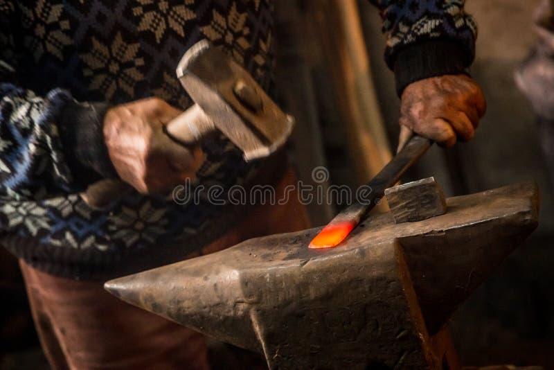 Stary blacksmith ręcznie fałszuje stopionego metal z młotem na kowadle fotografia royalty free