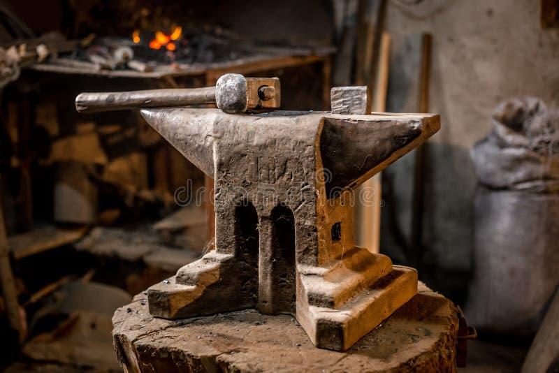 Stary blacksmiths młot na kowadle w warsztacie czyta używać dla fałszować żelazo obrazy royalty free