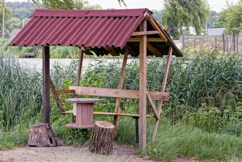 Stary brown drewniany gazebo roślinność na brzeg rezerwuar i zdjęcia stock