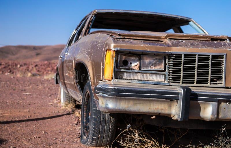 Stary brown samochód z psującym reflektorem płaską oponą w pustyni pod niebieskim niebem i zdjęcie royalty free