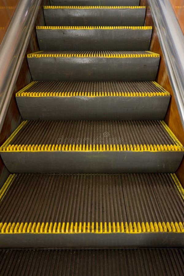 Stary brudny eskalator z żółtymi ostrzeżenie lampasami w metrze zdjęcia stock