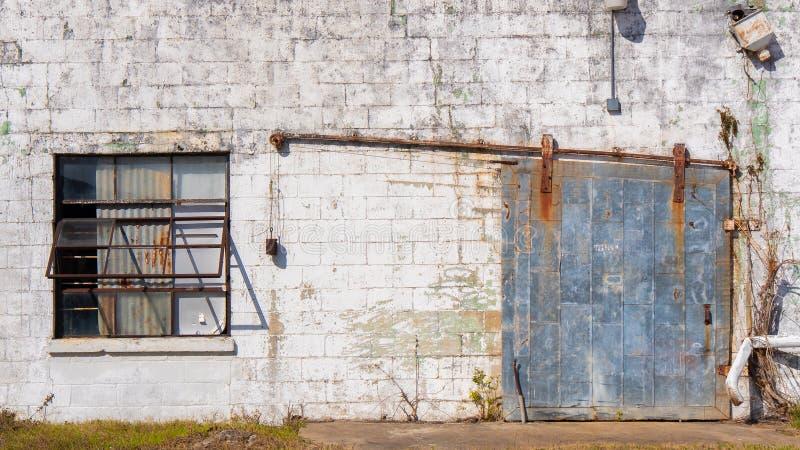 Stary budynek textured powierzchnię z ośniedziałym stalowym drzwi i okno obrazy royalty free