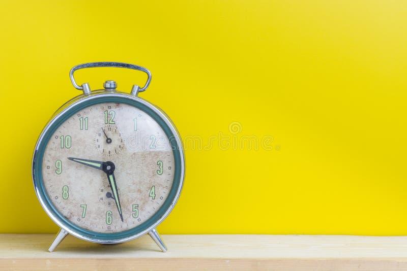 Stary budzik, żółty tło zdjęcia royalty free