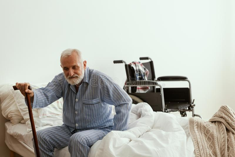 Stary chory mężczyzna z jest ubranym błękitne piżamy w domu, obsiadanie na łóżku i zdjęcia stock