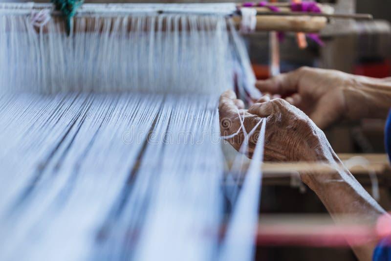 Stary człowiek ręka, Tajlandzki tradycyjny tkactwo, szczegół tkactwa krosienko dla domowej roboty jedwabiu Używać dla jedwabnicze zdjęcie royalty free