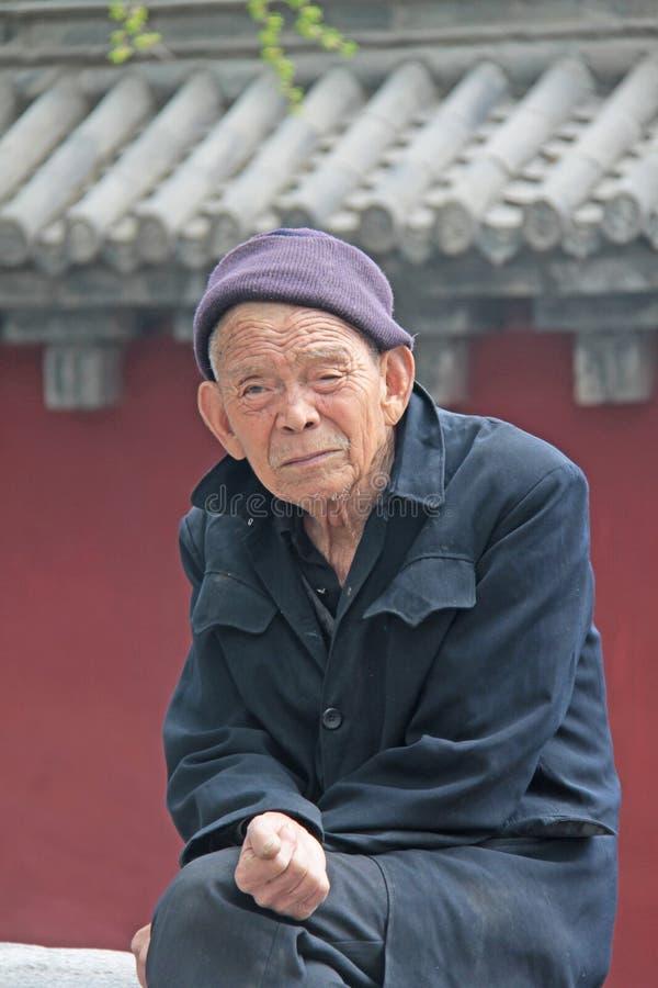 Stary człowiek z dużymi ucho i kapeluszem siedzi w monasterze Shaolin, Chiny zdjęcie royalty free