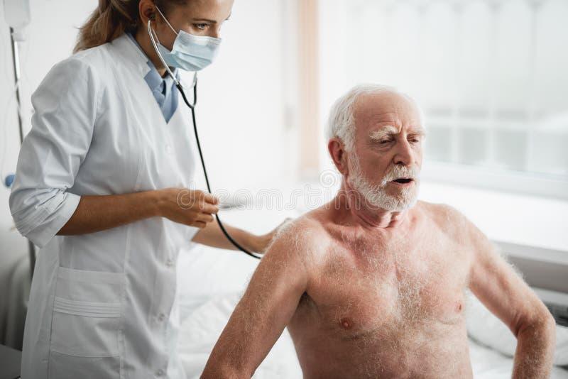 Stary człowiek bierze długiego oddech podczas badania medycznego fotografia royalty free