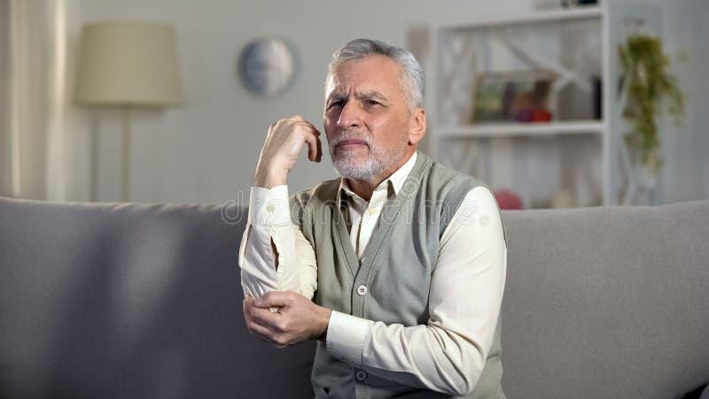 Stary człowiek czuje ostrego ból w łokciu, objawy artretyzm, wiązadło uraz obrazy stock