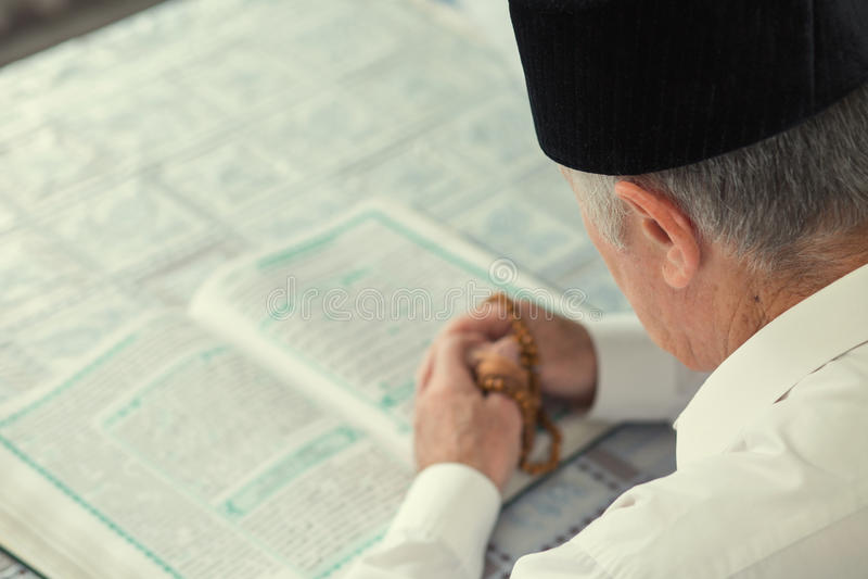 Stary człowiek czyta Koran obraz stock