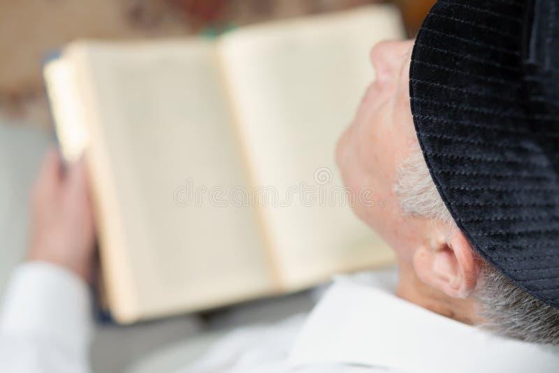 Stary człowiek czyta Koran Selekcyjna ostrość obrazy stock