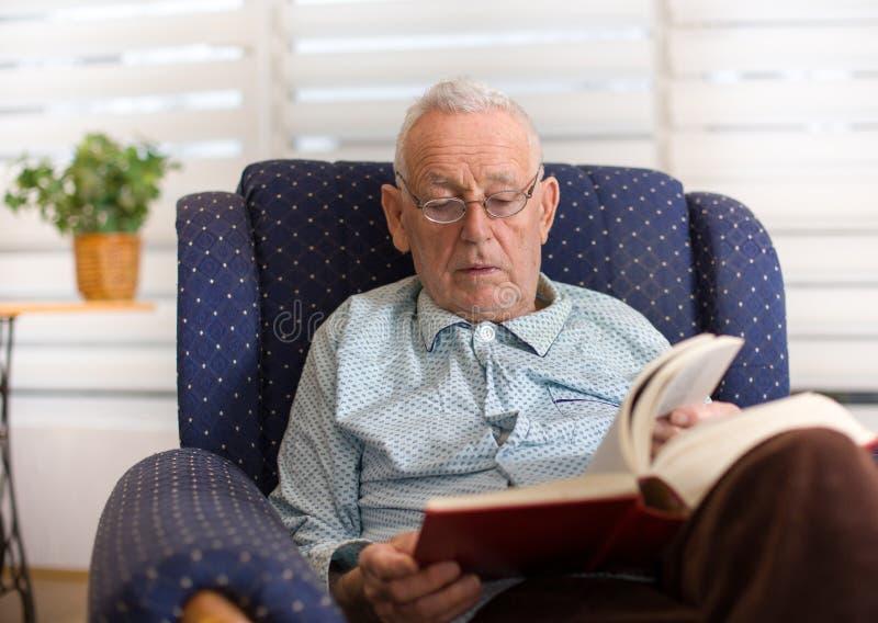 Stary człowiek czytelnicza książka w domu fotografia stock