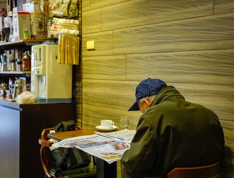 Stary człowiek czytelnicza wiadomość przy sklep z kawą obraz royalty free