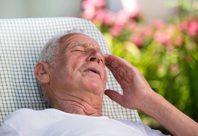 Stary człowiek ma migrenę w ogródzie zdjęcia stock