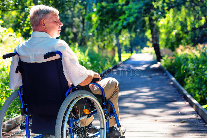 Stary człowiek na wózku inwalidzkim na ścieżce w parku obraz royalty free