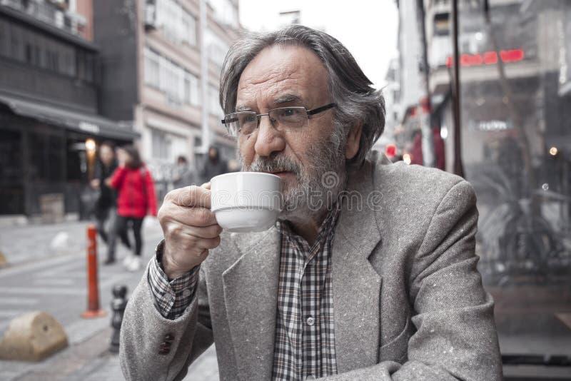 Stary człowiek pije kawę wewnątrz outdoors zdjęcia royalty free
