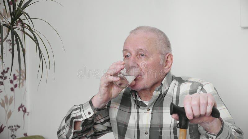 Stary człowiek pije szkło wody zdrowy styl życia 4k indoors w domu zdjęcia stock