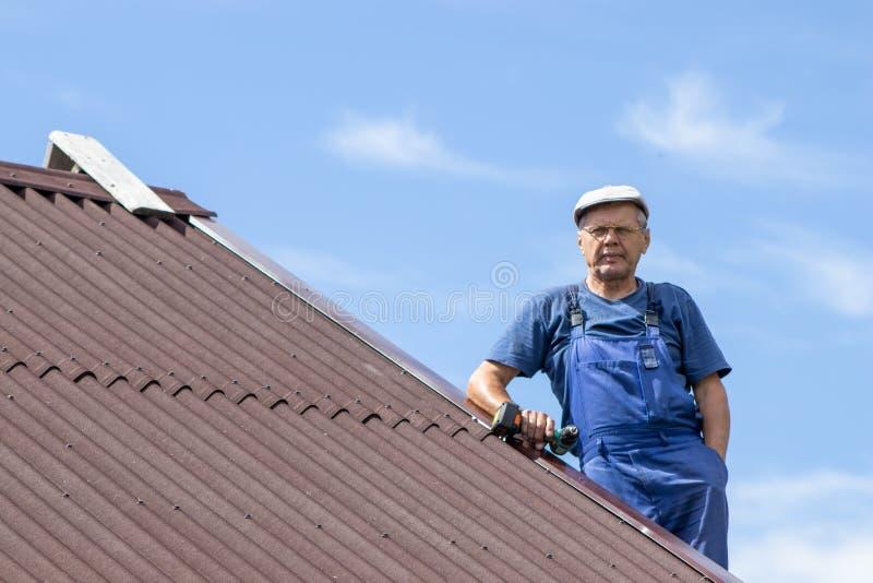 Stary człowiek pracuje z elektrycznym śrubokrętem na dachu dom bez zbawczej nicielnicy, jest ubranym prac ubrania, błękitny kombi fotografia stock