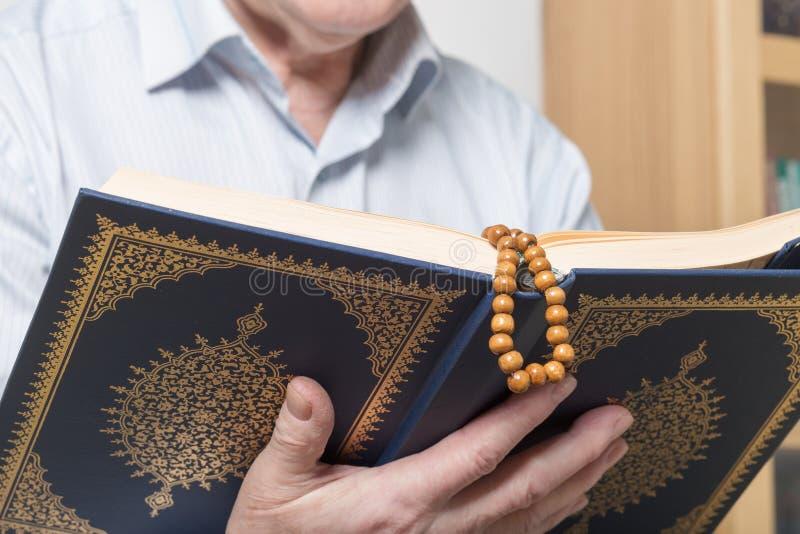 Stary człowiek ręka z różanów koralikami trzyma Koran obrazy stock
