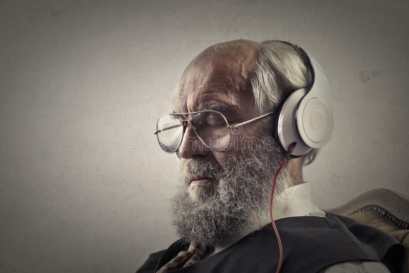Stary człowiek słucha muzyka zdjęcia royalty free
