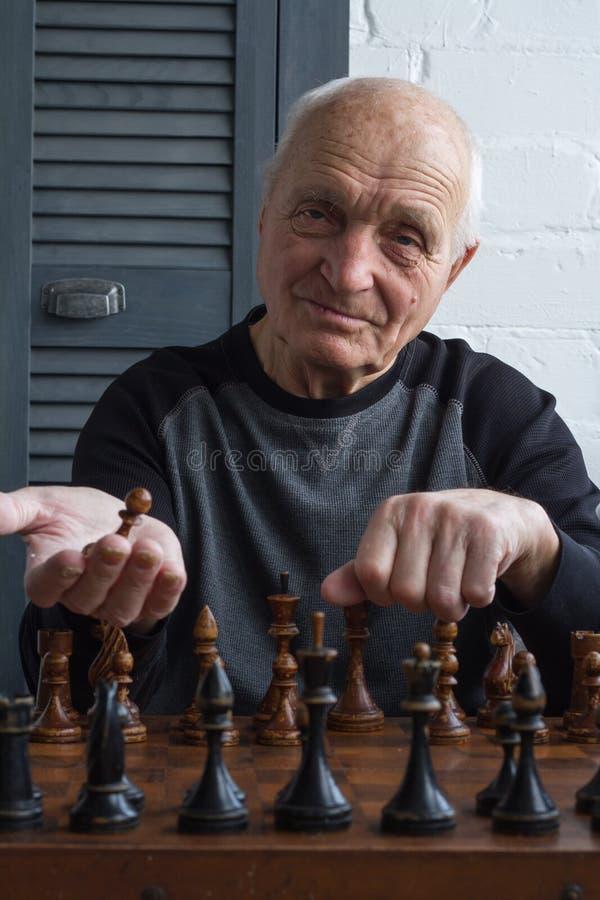 Stary cz?owiek siedzi przed chessboard i robi pierwszy ruchowi w gr?, g??wkowanie fotografia stock