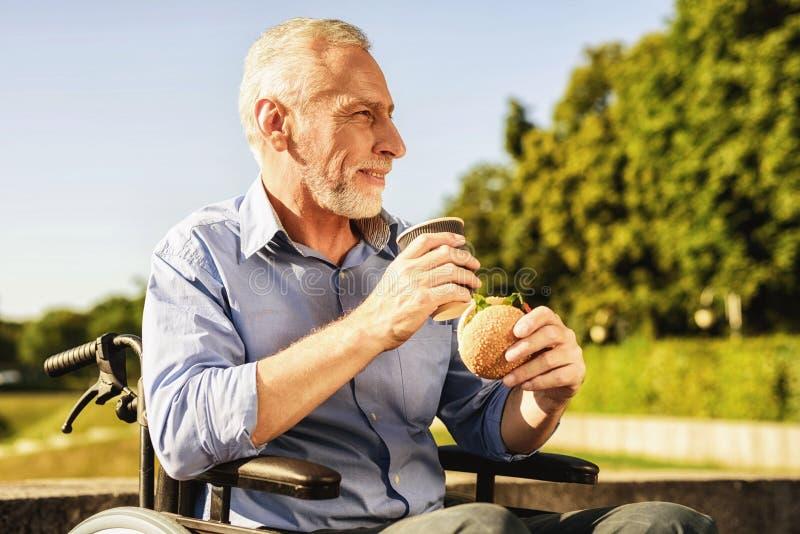 Stary człowiek siedzi w jeść i wózku inwalidzkim Ono uśmiecha się fotografia stock
