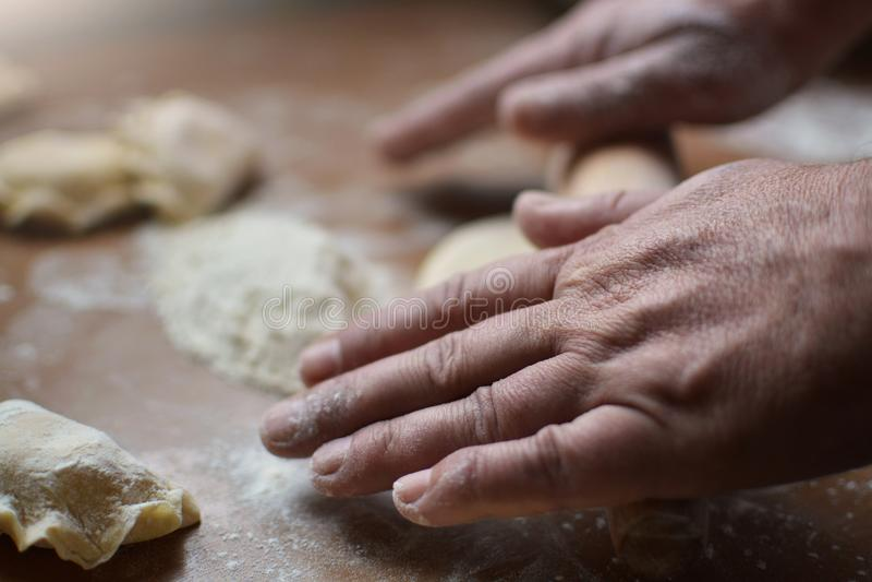 Stary człowiek stacza się ciasto surowe ręki fotografia stock