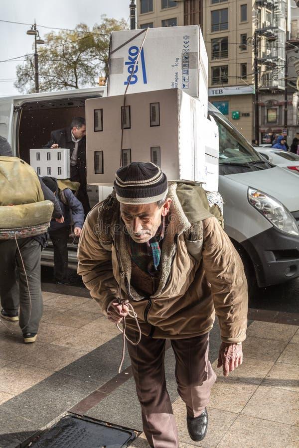 Stary człowiek, starszy pracownik, dostarczający ciężkiego pakunek, trzyma ogromnego pakuneczek na jego z powrotem, podczas śnież zdjęcia royalty free