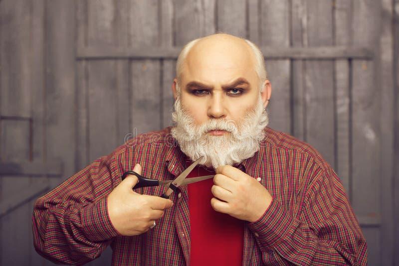 Stary człowiek tnąca broda z nożycami zdjęcia royalty free