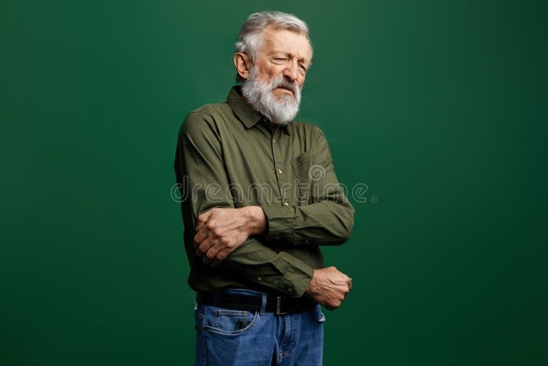 Stary człowiek trzyma jego łokieć w bólu w zielonej koszulce i cajgach z zamkniętymi oczami obraz royalty free