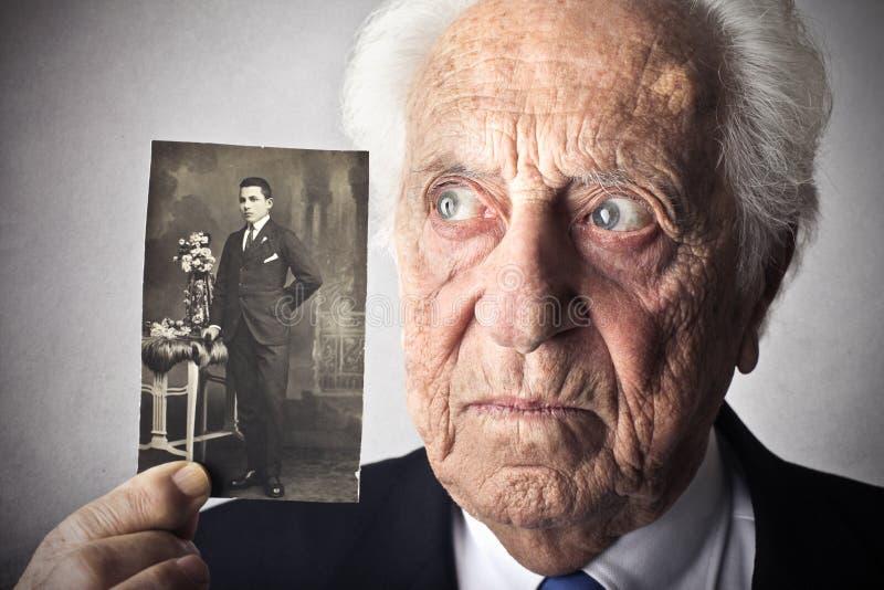 Stary człowiek trzyma jego obrazek obraz royalty free